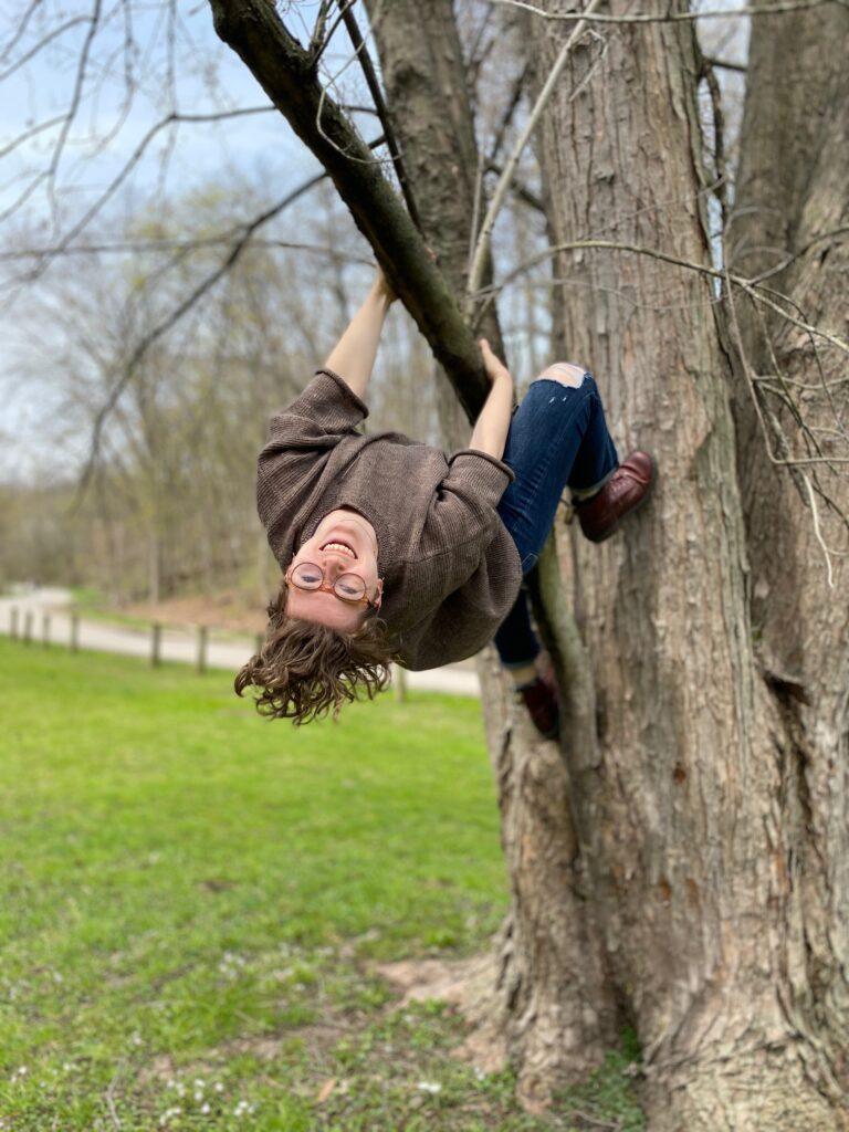 Lex smiling hanging upside down from a tree in a park.