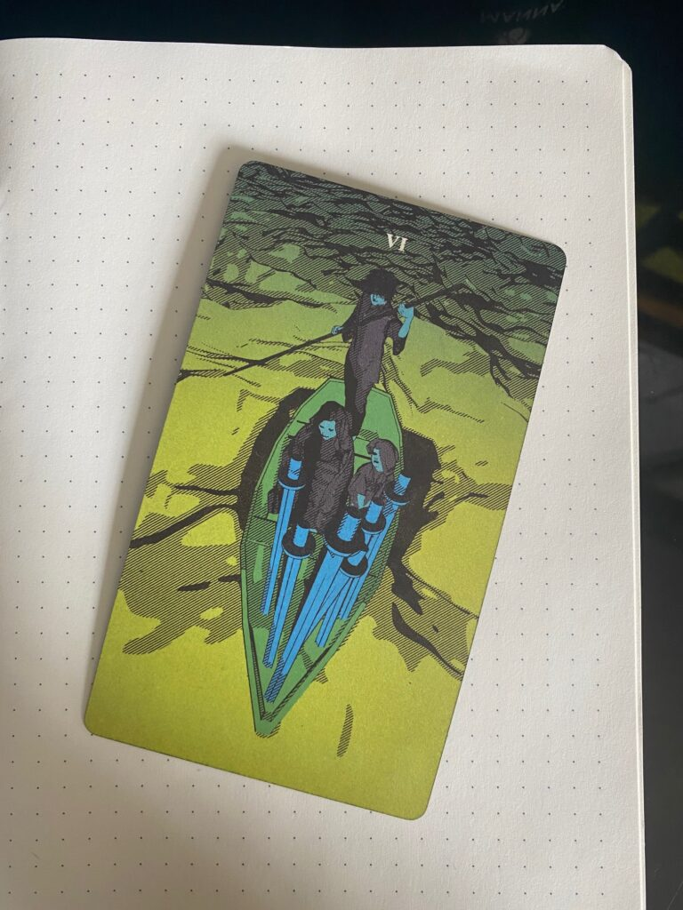 Image shows the 6 of Swords card from the Tarot of the Holy Spectrum atop a blank notebook page. Card shows two people being ferried across a river, from choppy water to smooth water. 6 swords are in the bow of the ferry. In the stern, the ferrier stands above the two passengers.